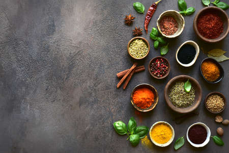 Set of natural organic asian spices in a bowls on a dark slate, stone or concrete background. Top view with copy space.