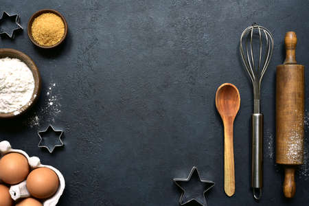 Culinary background with ingredients for baking: sugar, eggs, flour on a black slate, stone or concrete background. Top view with copy space.