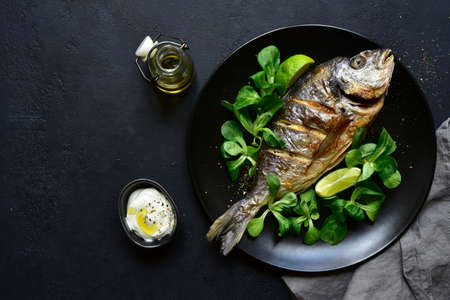 Grilled dorado or sea bream on a plate over black slate, stone or concrete background. Top view with copy space. Archivio Fotografico