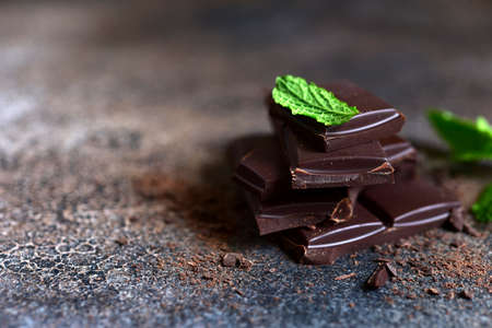 Dark chocolate slices with fresh mint on a slate, stone or concrete background.