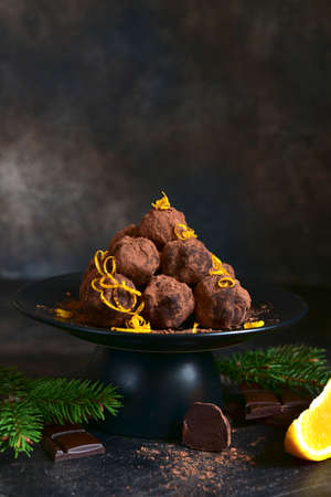 Delicious chocolate truffles with orange on a black plate on a dark slate, stone or concrete background.