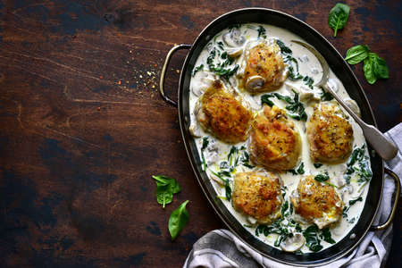 Chicken thigh stew in cream sauce with mushrooms and spinach in a skillet on a dark wooden background. Top view with copy space.