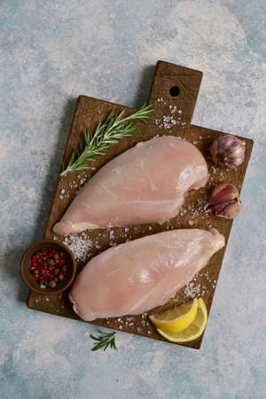 Raw chicken breast with ingredients for making on a wooden cutting board on a light blue slate, stone or concrete background. Top view with copy space.