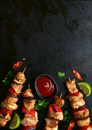 Roasted chicken kebab with ketchup on a black metal tray. Top view with copy space.