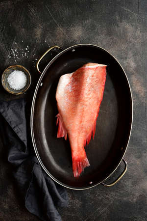Raw organic sea perch in a skillet on a dark slate, stone or concrete background. Top view with copy space.