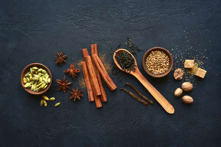 Ingredients for making traditional indian tea masala on a dark slate, stone or concrete background. Top view with copy space.