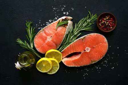 Fresh organic salmon slices with ingredients for making: lemon, spices and olive oil on a black slate, stone or concrete background. Top view with copy space.