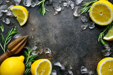 Fresh ingredients for making lemonade or lemon cocktail on a dark slate, stone or concrete background. Top view with copy space. Archivio Fotografico