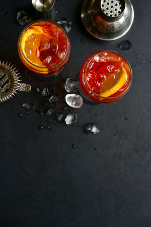Delicious italian cocktail with orange in a glasses on a black slate, stone or concrete background. Top view with copy space. Archivio Fotografico