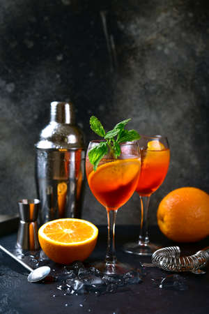Delicious italian cocktail with orange in a glasses on a black slate, stone or concrete background.