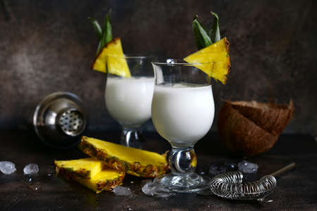 Pina colada - tropical pineapple coconut cocktail with white rum and cream in a glasses on a darl slate, stone or concrete background.