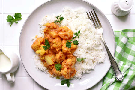 Vegan cauliflower curry with rice on a plate over white slate, stone or concrete background. Top view with copy space.