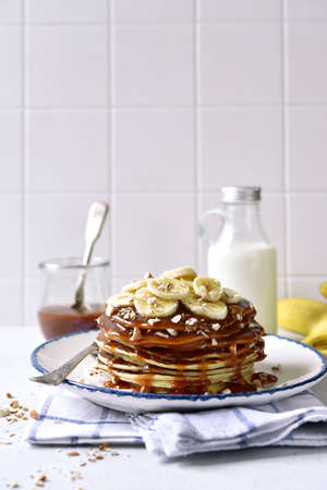 Delicious hot banana pancakes with caramel sauce and nuts on a white slate, stone or concrete background.