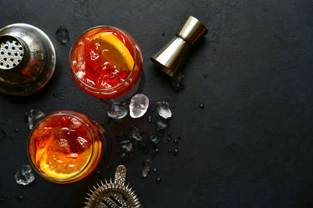 Delicious italian cocktail with orange in a glasses on a black slate, stone or concrete background. Top view with copy space