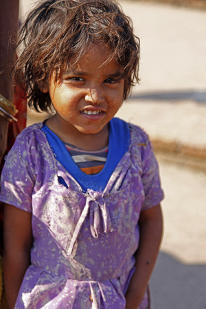 neighborly: GAYA, INDIA - MARCH 19: Indian child girl smiles and be shy in a village in Gaya, India on March 19, 2015.