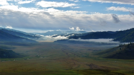 Morning fog hanging over Mountain Range and valley at Kanas, Xinjiang, China photo