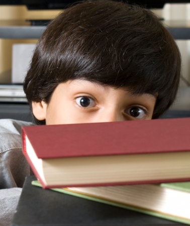 surprised boy behind books photo