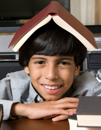 happy boy with book over his head photo