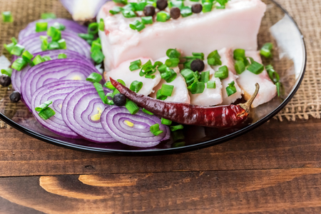 beautifully: Fresh pork fat, with red hot chili peppers, green and purple onions and  peas allspice beautifully laid out on a glass plate on the