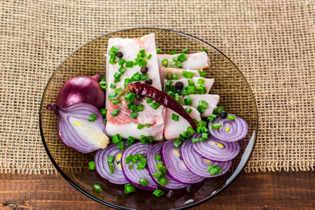 Fresh pork fat, with red hot chili peppers, green and purple onions and  peas allspice beautifully laid out on a glass plate