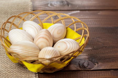 Beautiful wooden Easter eggs are in a wicker nest on old wooden background