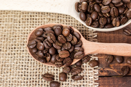 whole coffee beans in a wooden spoon and a scattering of coffee beans on burlap Stock Photo