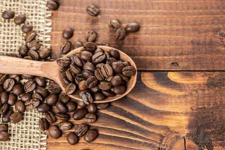 whole coffee beans in a wooden spoon and a scattering of coffee beans on burlap and old brown boards with free space for your text Stock Photo