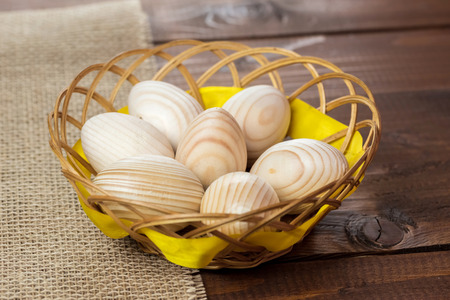 Beautiful wooden Easter eggs are in a wicker nest on old wooden background with free space for your text