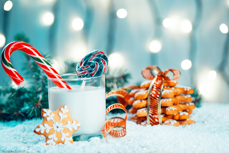 Christmas gingerbread and milk with decorations, snow, christmas tree branches on bokeh blurred lights background.