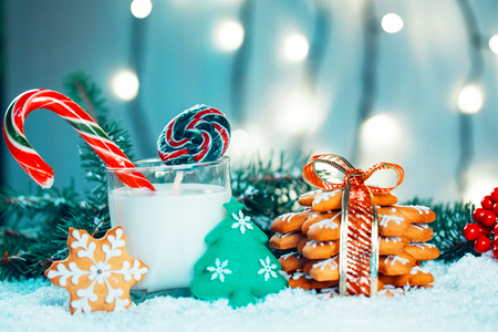 Christmas gingerbread and milk with decorations, snow, christmas tree branches on bokeh blurred lights background. Free space