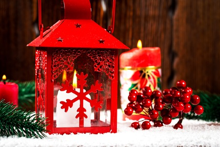 Christmas and New Year background with Christmas candle lantern and Christmas tree branches, snow and decorations, wooden wall behind. Free space