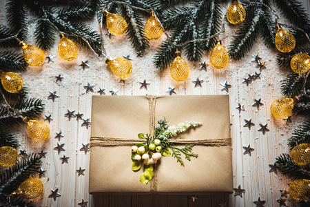 Christmas gift box with a bow and a beautiful glowing garland against the white wooden background with branches of a Christmas tree, snow and silvery stars. Holiday Merry Christmas greeting card.
