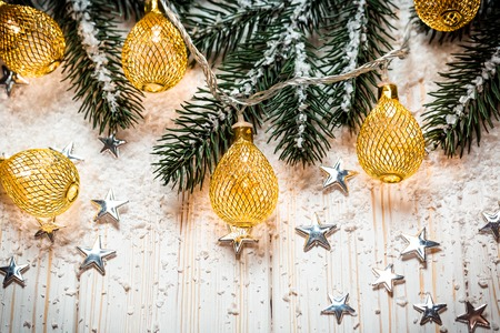 Christmas background with a luminous garland on white wooden table with the branches of the Christmas tree, stars and snow. holiday idea for winter postcards and posters. Free space, golden frame Stock Photo