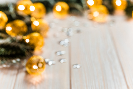 Christmas blurred background with a glowing garland golden bokeh on white wooden table. A beautiful holiday idea for postcards and posters. Free space, frame
