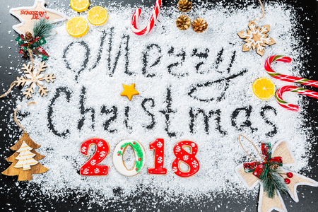 Merry Christmas inscription on snow with gingerbread snowflakes and 2018, candy, toys and New Year decor on a black background. Beautiful Holiday Frame