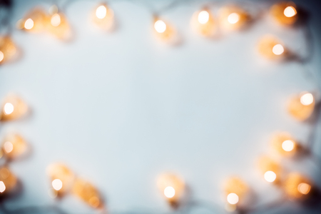 Christmas blurred background with a glowing garland golden bokeh on white. A beautiful holiday idea for postcards and posters. Free space, frame