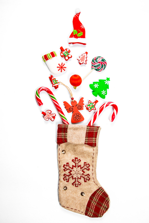 Christmas background with a sock from which scattered gifts, candy, New Year decorations toys on a white background. The concept of advertising, shopping, discounts and gifts for the winter holidays Standard-Bild