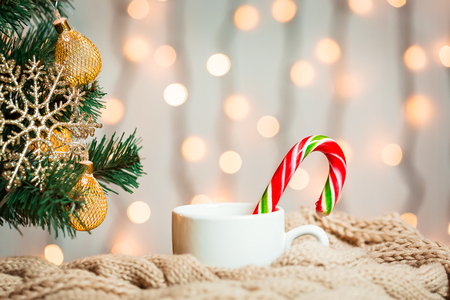 A Christmas tree decorated snowflakes and a garland, cup of coffee, candy with knitted scarf on the background of a bokeh and white boards.