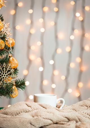 A Christmas tree decorated snowflakes and a garland, cup of coffee with knitted scarf on the background of a bokeh and white boards.