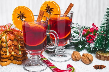 Christmas glass of red mulled wine on table with cinnamon sticks, branches of Christmas tree, snow, gingerbread, cone, candy, New Year decorations on white wooden background.  Standard-Bild