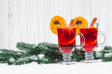 Christmas glass of red mulled wine on table with cinnamon sticks, branches of Christmas tree and snow on white wooden background. Free space