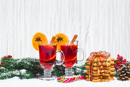 Christmas glass of red mulled wine on table with cinnamon sticks, branches of Christmas tree, snow, gingerbread,  New Year decorations on white wooden background. Free space