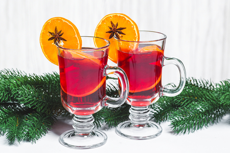 Christmas glass of red mulled wine on table with cinnamon sticks, branches of Christmas tree  on white wooden background. Free space