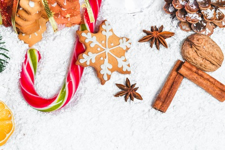 Christmas background with gingerbread cookie, snow and branches of a Christmas tree.