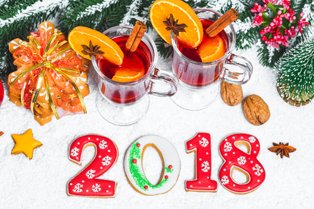 Christmas glass of red mulled wine on table with cinnamon sticks, branches of Christmas tree, snow, gingerbread 2018, cone, candy, New Year decorations on white wooden background. Free space Standard-Bild