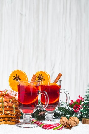 Christmas glass of red mulled wine on table with cinnamon sticks, branches of Christmas tree, snow, gingerbread, cone, candy, New Year decorations on white wooden background. Free space Standard-Bild