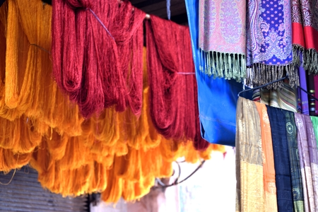 unrefined: Colored Moroccan scarves on right of the image and unrefined colored wool on left of the image, hanged in the Arabian market