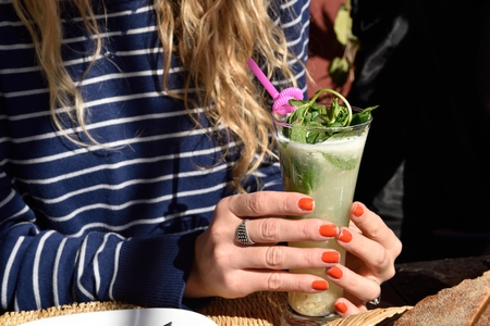 striped shirt: Female hands with red nail polish hold a long glass of cocktail with lemon garnish and pink straw. There are a blue and white striped shirt and blonde hair on background