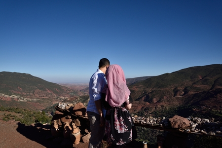 twosome: Couple looks back turned rock desert. She has tipical and religious pink veil.
