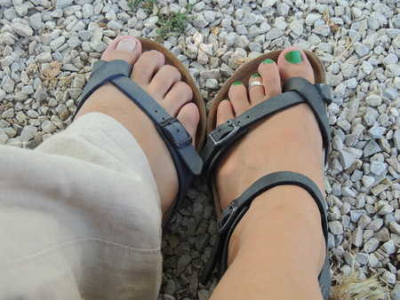 put on: Couple of feet, one female and one male, put on dark gray sandals, gray pebbles on the background